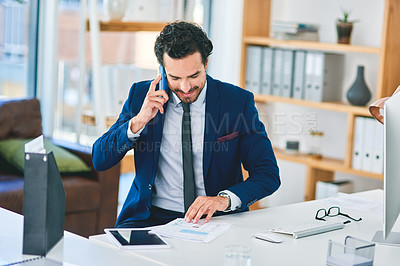 Buy stock photo Shot of a young businessman talking on a cellphone while going through paperwork in an office