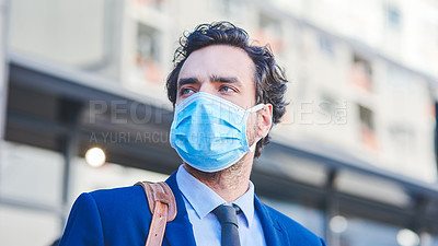 Buy stock photo Shot of a young businessman wearing a mask while out in the city