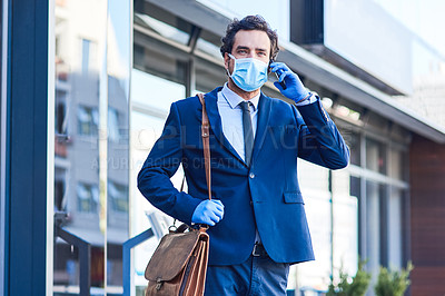 Buy stock photo Shot of a young businessman wearing a mask and talking on a cellphone while out in the city