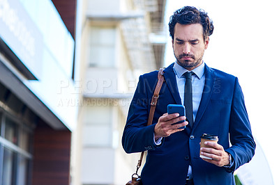 Buy stock photo Shot of a young businessman using a cellphone while out in the city