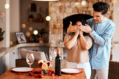 Buy stock photo Shot of a man surprising his wife with a romantic dinner at home