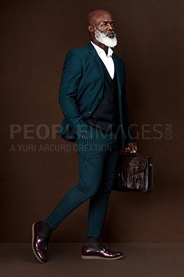Buy stock photo Studio shot of a well-dressed businessman carrying his briefcase against a brown background