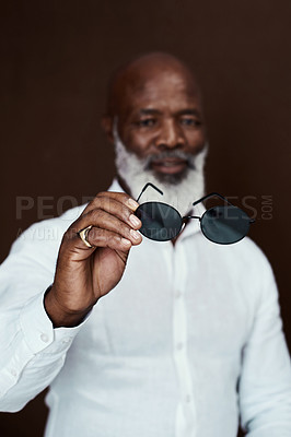 Buy stock photo Studio shot of a mature businessman posing against a brown background