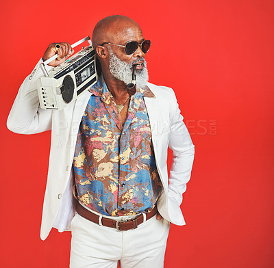 Buy stock photo Studio shot of a senior man wearing vintage clothing while posing with a boombox against a red background