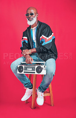 Buy stock photo Studio shot of a mature man holding a boombox while sitting against a red background