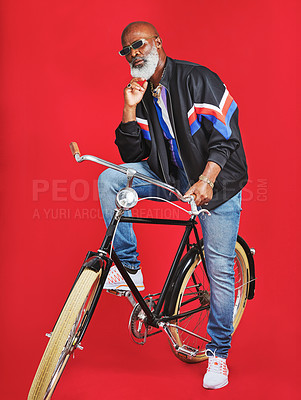 Buy stock photo Shot of a senior man sitting on a vintage bicycle against a red background
