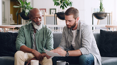 Buy stock photo Shot of two businessmen going through paperwork together in an office