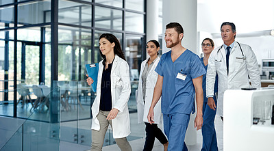 Buy stock photo Shot of a group of doctors walking through a modern hospital