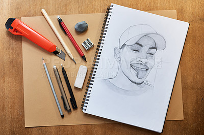 Buy stock photo Shot of a pencil drawing and other various artistic tools on a table