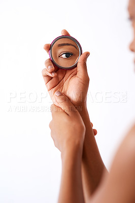 Buy stock photo Studio shot of an unrecognizable woman holding a pocket size mirror against a white background