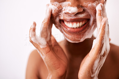 Buy stock photo Studio shot of an unrecognizable woman washing her face against a white background