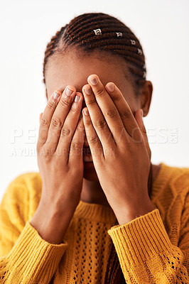 Buy stock photo Studio shot of a woman holding her hands over her face while standing against a white background