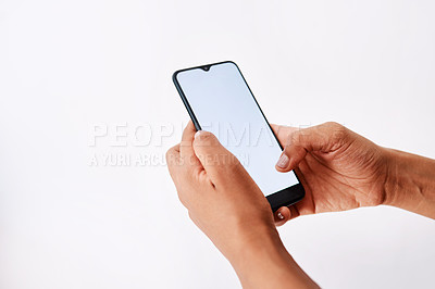 Buy stock photo Studio shot of an unrecognizable woman holding a cellphone against a white background