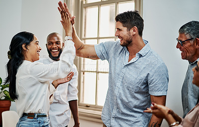 Buy stock photo Shot of a group of businesspeople giving each other high five in a modern office