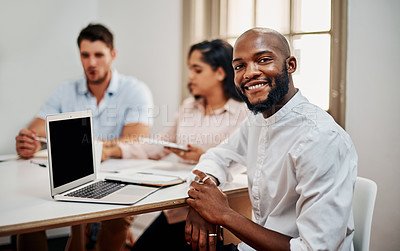 Buy stock photo Portrait of a young businessman having a meeting with colleagues in a modern office