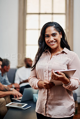 Buy stock photo Shot of a young businesswoman using a digital tablet with her colleagues in the background