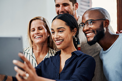 Buy stock photo Cropped shot of a group of business colleagues taking selfies with a tablet in the office