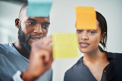 Buy stock photo Cropped shot of two young business colleagues brainstorming on a glass wipe board in their office