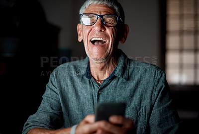 Buy stock photo Shot of a senior businessman using a cellphone in an office at night
