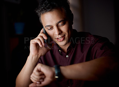 Buy stock photo Shot of a young businessman checking the time on his watch while talking on a cellphone in an office at night