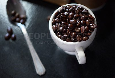 Buy stock photo Studio shot of coffee beans in a cup and on a spoon