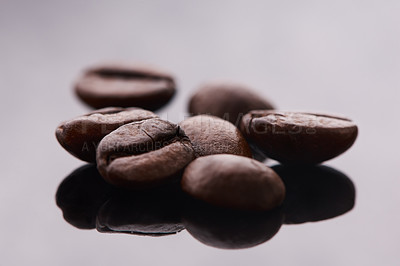 Buy stock photo Studio shot of coffee beans against a grey background