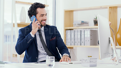 Buy stock photo Shot of a young businessman talking on a cellphone while working on a computer in an office