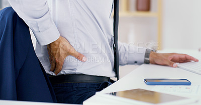 Buy stock photo Closeup shot of an unrecognisable businessman suffering with back pain while working in an office