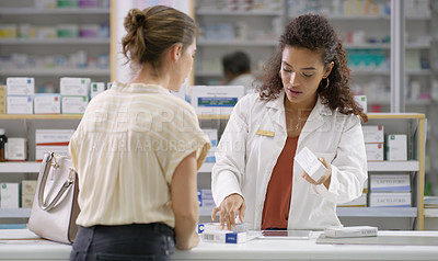Buy stock photo Shot of a pharmacist assisting a young woman in a chemist