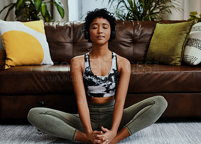 Buy stock photo Shot of a young woman listening to music while meditating at home