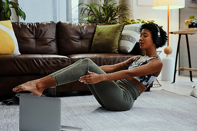 Buy stock photo Shot of a young woman wearing headphones and using a laptop while exercising at home