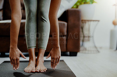 Buy stock photo Closeup shot of an unrecognisable woman touching her toes while exercising at home