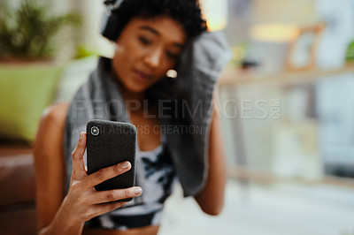 Buy stock photo Shot of a young woman using a cellphone and wiping her face with a towel while exercising at home