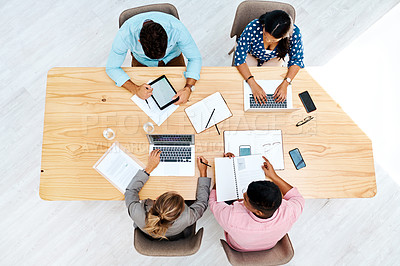 Buy stock photo High angle shot of a group of businesspeople working together at a table in an office