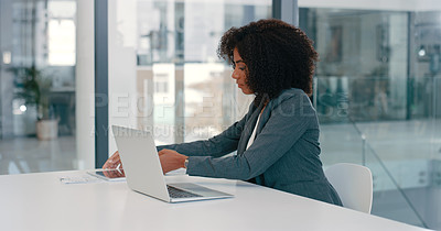 Buy stock photo Shot of a young businesswoman using a laptop and digital tablet at her desk in a modern office