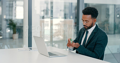 Buy stock photo Shot of a young businessman using hand sanitiser before working with his laptop in a modern office