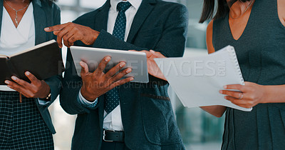 Buy stock photo Cropped shot of a group of young businesspeople using a digital tablet during a discussion in a modern office