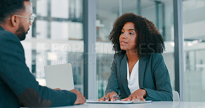 Buy stock photo Shot of a young businessman and businesswoman filling out paperwork during a meeting in a modern office