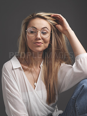 Buy stock photo Studio shot of a beautiful young woman sitting against a brown background