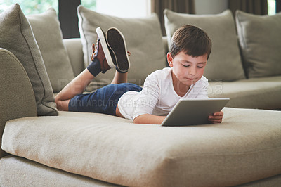 Buy stock photo Shot of an adorable little boy using a digital tablet on the sofa at home