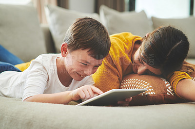 Buy stock photo Shot of an adorable little boy using a digital tablet with his mother on the sofa at home