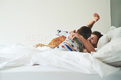Buy stock photo Shot of an adorable little boy waking his father up in bed in the morning at home