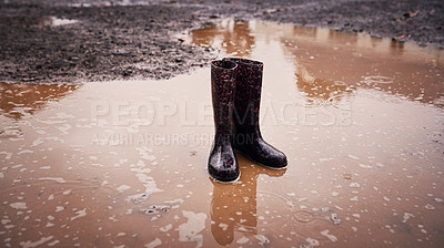 Buy stock photo Shot of two rain boots standing in a puddle of muddy water