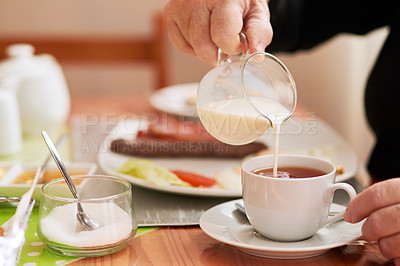 Buy stock photo Closeup shot of an unrecognisable woman pouring milk into a cup of tea at home