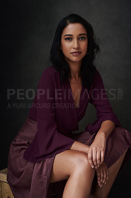 Buy stock photo Studio shot of a beautiful young woman sitting against a grey background
