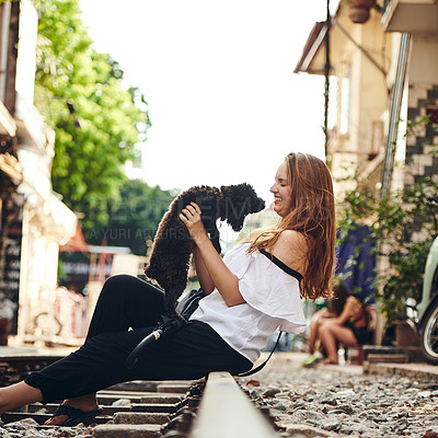 Buy stock photo Shot of a young woman playing with a dog while exploring a foreign city