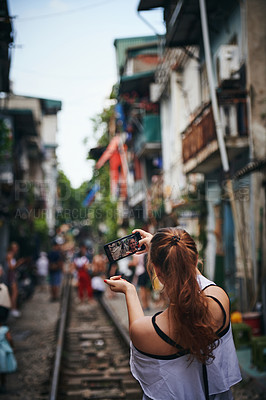Buy stock photo Cropped shot of a young woman taking selfies while exploring a foreign city