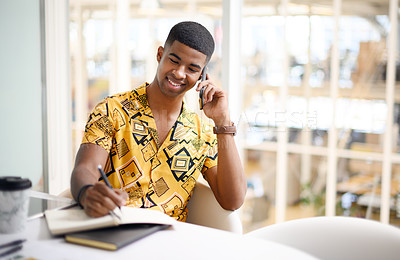 Buy stock photo Shot of a young businessman writing notes while talking on a cellphone in an office