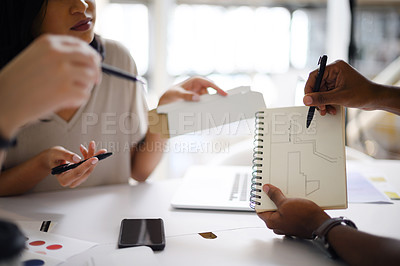 Buy stock photo Closeup shot of a group of unrecognisable businesspeople analysing blueprints together in an office