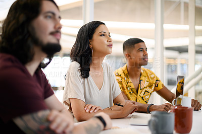 Buy stock photo Shot of a young businesswoman sitting alongside her colleagues during a presentation in an office